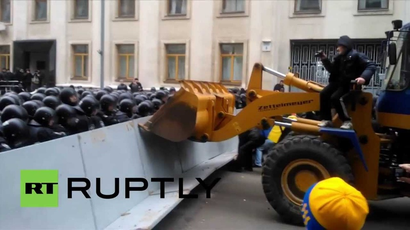 Ukraine Protesters throw flares as a digger is driven through police barricade